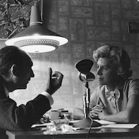 Judith Jasmin et Jean Vilar discutent autour d'une table.