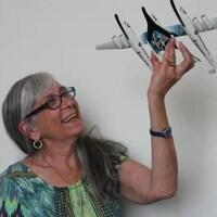 Judy Anderson tient un modèle réduit d'une navette spatiale. Elle est photographiée devant un mur gris.