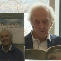 Jules Bélanger lit la biographie écrite par Sylvain Rivière devant une fenêtre.