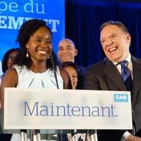 Julie Séide et François Legault, souriants, derrière un podium où on peut lire «Maintenant.».