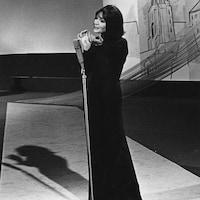 Juliette Greco chantant seule sur scène au micro dans une robe longue.