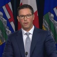 Un homme en costume cravate parle sur un podium devant une rangée de drapeaux de l'Alberta et du Canada.