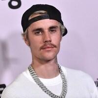Justin Bieber porte une moustache, une casquette noire et un chandail blanc.