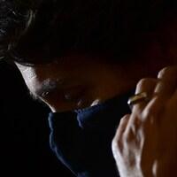 Le premier ministre Justin Trudeau ajuste son couvre-visage noir dans la pénombre.