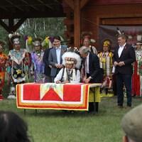 Le chef de la Première Nation Cowessess, Cadmus Delorme, signe un accord visant à placer sous la responsabilité de la Première Nation ses enfants et ses familles dans le besoin. Il est accompagné du premier ministre du Canada, Justin Trudeau, et du premier ministre de la Saskatchewan, Scott Moe, le 6 juillet 2021.