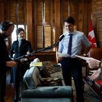 Le premier ministre Justin Trudeau qui lit un script, dans son bureau, avec des techniciens de son équipés d'une perche de microphone, et le créateur de <em>Corner Gas</em>, Brent Butt (à droite).