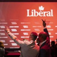 Deux jeunes hommes célèbrent la victoire de leur formation politique en levant la main vers le ciel.