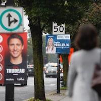 Une femme marche sur une rue où des affiches électorales sont accrochées.