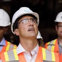 Justin Trudeau porte un casque de construction et des lunettes de protection. Il regarde vers le haut.