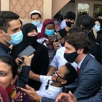Justin Trudeau prend une photo avec un enfant, au milieu de plusieurs personnes masquées.