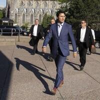 Justin Trudeau marche entouré de gardes de corps.