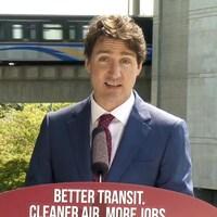 Justin Trudeau devant un Skytrain qui passe.