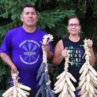 Une femme et un homme mohawks tiennent des tresses de maïs jaune et bleu.
