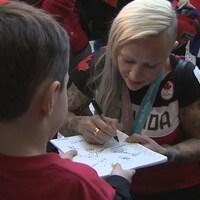 Elle signe des autographes à son retour à Calgary.