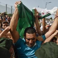 Il est au milieu d'une foule portant le drapeau algérien.