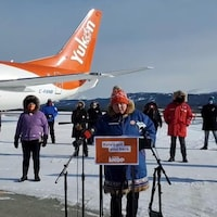 Kate White sur le podium. Derrière elle se trouvent des partisans du NPD et un avion d'Air North.