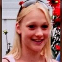Une fille aux cheveux blonds avec des lunettes sur sa tête. Elle est sourante.