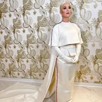 Katy Perry porte une longue robe blanche avec des boutons rouges et des boutons bleus.