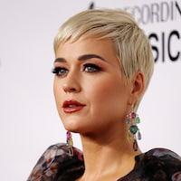 Katy Perry porte des cheveux blonds courts et des grosses boucles d'oreilles.