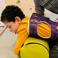 Kayden Kot fait des exercices pour son dos avec l'aide d'un homme.