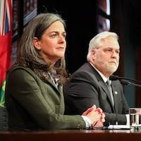 Une femme et un homme en arrière-plan à ses côtés dans une salle de presse de l'assemblée législative de l'Ontario.