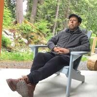 Un homme assis sur chaise devant des arbres.
