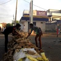 Des manifestants érigent une barricade le long d'une rue lors de manifestations dans le centre de Khartoum.