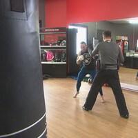 Une nouvelle école de kickboxing ouvre ses portes à Sherbrooke. On voit ici deux hommes pratique ce sport devant des miroirs. Le kickboxing est une combinaison de coups de poing et de coups de pied.