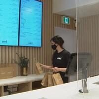 Une femme place des sacs sur un comptoir dans une boutique.