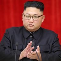 Un homme au regard sérieux et qui porte des lunettes s'apprête à faire un discours.
