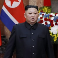 Kim Jong-un devant un drapeau.