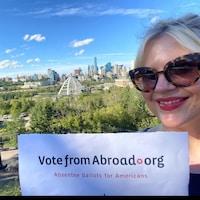 Kimberly Jonhson pose devant la ville d'Edmonton avec une pancarte votefromabroad.org.