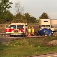 Photo d'un camion de pompier et d'un camion à côté d'une pile de débris recouverts par une bâche bleue.