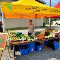 Une femme sourit derrière un kiosque avec une table remplie de légumes.