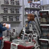 Deux dames parlent d'un livre devant un kiosque au 35e Salon du livre de la Côte-Nord.
