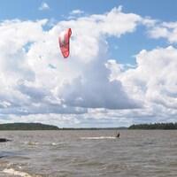 Un homme fait du kite-surf sur un lac.