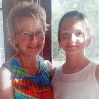 Klara et sa grand-mère se tiennent côte à côte devant une fenêtre et sourient à la caméra.