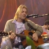 Kurt Cobain assis, chante et joue de la guitare.