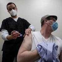 Un pharmacien administre une dose de vaccin à un patient.