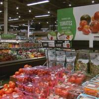 Des comptoirs de fruits et légumes dans un supermarché.