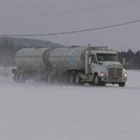 Un camion-citerne transportant du lait sur une route de campagne en hiver.