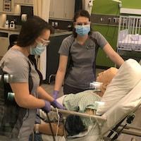 Deux étudiantes en soins infirmiers du Cégep de Chicoutimi aux côtés d'un mannequin