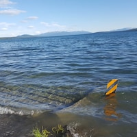 De l'eau submerge un petit bateau à quai sur le lac Marsh, au Yukon.