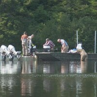 Des équipes enlèvent des barils de roténone des bateaux pour les emporter.