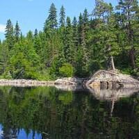 Image d'un lac avec eau calme, noire et profonde; sapins et conifères proches d'une berge rocailleuse.