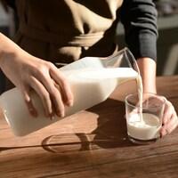Une femme se verse un verre de lait.