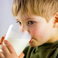 Un petit garçon boit un verre de lait.