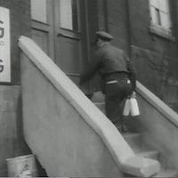 Un laitier en uniforme monte des escaliers avec deux bouteilles de lait en verre.