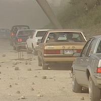 Des voitures sont en file. Des dizaines de roches et de débris jonchent le sol.