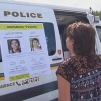 Une femme regarde une fourgonnette de police sur laquelle il y a une affiche avec les photos et les descriptions de deux jeunes femmes autochtones disparues